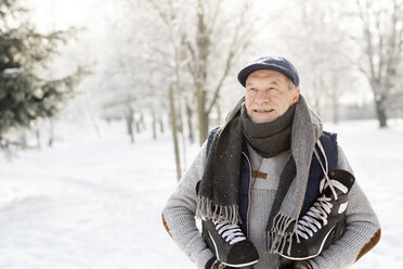 Smiling senior man with ice skates in winter forest - HAPF02141