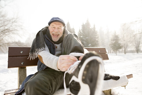 Portrait of happy senior man sitting on bench in winter landscape putting on ice skates - HAPF02147