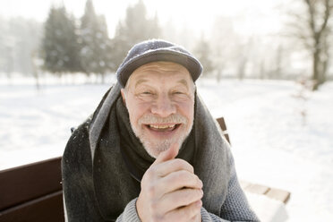 Portrait of happy senior man sitting on bench in winter landscape - HAPF02150