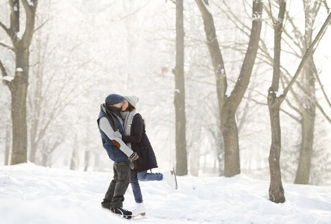 Senior couple hugging and kissing on frozen lake - HAPF02153