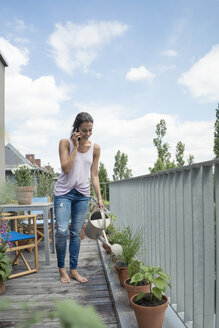 Woman on cell phone on balcony watering plants - JOSF01553