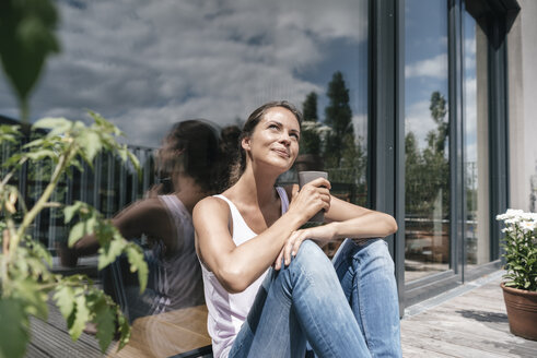 Smiling woman relaxing on balcony - JOSF01559