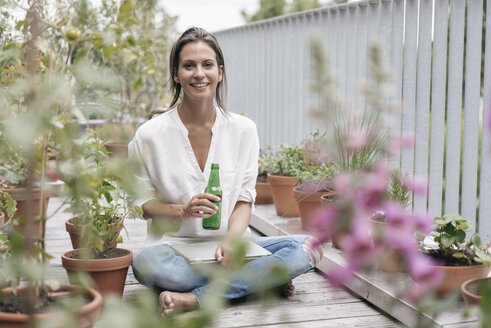 Smiling woman with bottle and laptop relaxing on balcony - JOSF01562