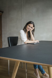 Portrait of smiling woman sitting at table with laptop - JOSF01565