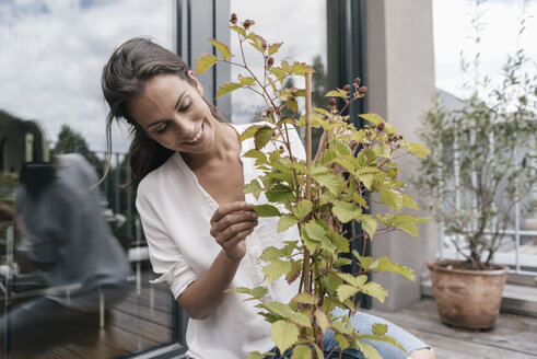 Smiling woman caring for plant on balcony - JOSF01571