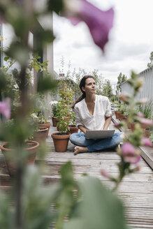 Woman sitting on balcony using laptop - JOSF01577