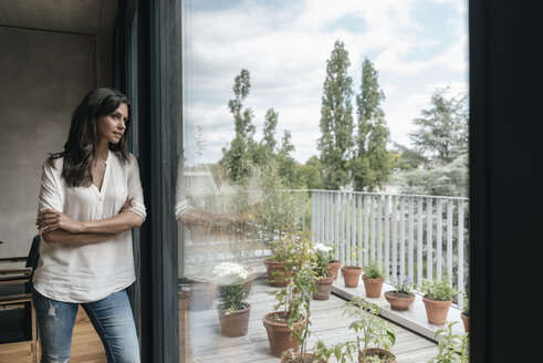 Woman at home looking out of window - JOSF01580