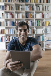 Portrait of smiling man at home holding tablet - JOSF01586