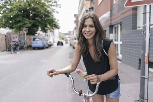 Smiling woman with ice lolly and bicycle - JOSF01604