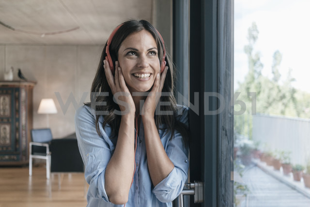 Smiling woman listening to music at home - JOSF01610
