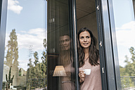 Smiling woman holding cup looking out of balcony door - JOSF01613