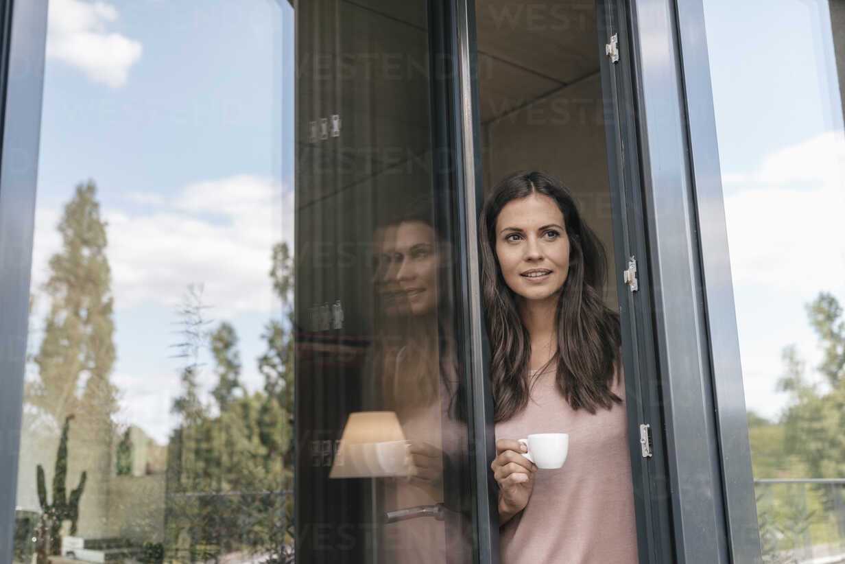 Smiling woman holding cup looking out of balcony door - JOSF01613 - Joseffson/Westend61