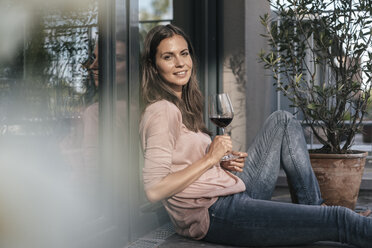 Woman with glass of red wine relaxing on balcony - JOSF01625