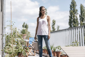 Smiling woman on balcony holding watering can - JOSF01628