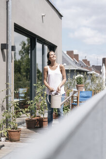 Smiling woman on balcony holding watering can - JOSF01631