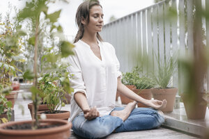 Woman sitting on balcony practicing yoga - JOSF01640