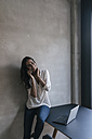 Portrait of smiling woman at concrete wall using cell phone - JOSF01661