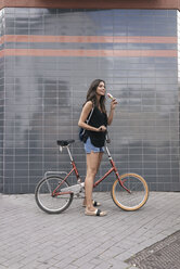 Smiling woman with ice lolly and bicycle - JOSF01667