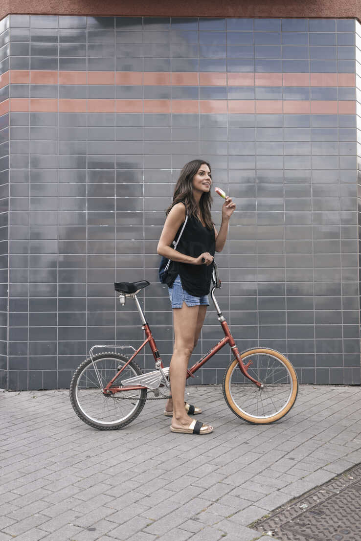 Smiling woman with ice lolly and bicycle - JOSF01667 - Joseffson/Westend61