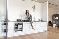 Smiling woman relaxing in kitchen at home - JOSF01670