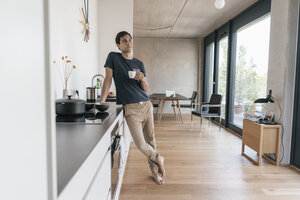 Young man holding cup of coffee in kitchen at home - JOSF01673