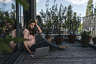 Woman with laptop sitting on balcony - JOSF01691