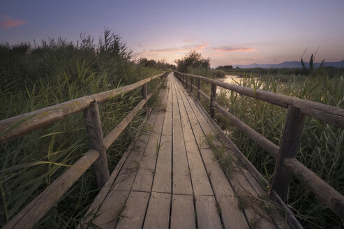 Spain, Alicante, empty boardwalk in a marsh at sunset - DHCF00156