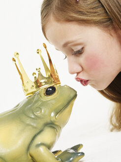 Portrait of little girl kissing frog king - FSF00962