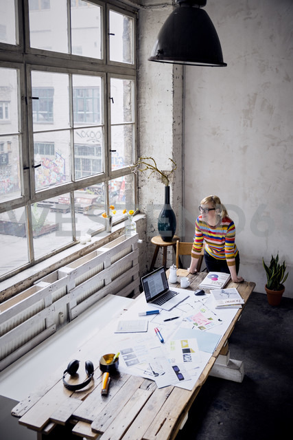 Woman standing at desk in a loft looking through window - RBF05954