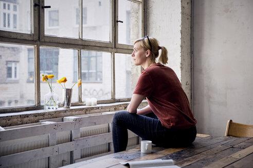 Woman sitting on desk in loft looking through window - RBF05957
