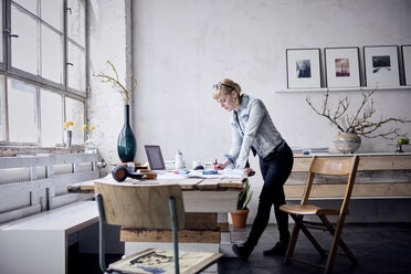 Woman working at desk in a loft - RBF05969