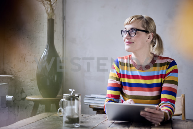 Portrait of smiling woman with tablet in a loft - RBF05984