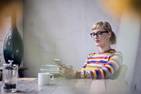 Portrait of smiling woman sitting at table with cup of coffee looking at cell phone - RBF05987