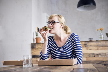 Portrait of smiling woman eating pizza - RBF05999