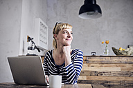 Portrait of smiling woman sitting at table with laptop and coffee mug - RBF06002