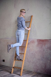 Smiling woman standing on ladder in an unrenovated room of a loft - RBF06011