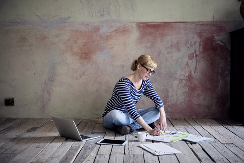 Woman sitting on wooden floor in an unrenovated room of a loft working - RBF06014