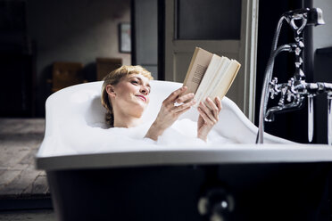 Portrait of relaxed woman taking bubble bath in a loft reading a book - RBF06020
