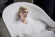 Portrait of woman with eyes closed taking bubble bath in a loft - RBF06023