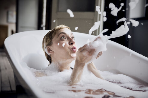 Blond woman taking bubble bath blowing foam in the air - RBF06026
