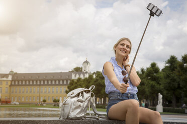 Germany, Karlsruhe, tourist taking selfie with selfie stick - JUNF00898