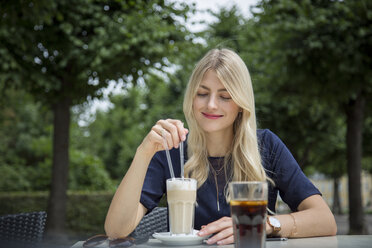 Portrait of blond woman sitting at sidewalk cafe with Latte Macchiato - JUNF00904