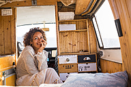 Spain, Tenerife, portrait of laughing woman sitting in van - SIPF01715