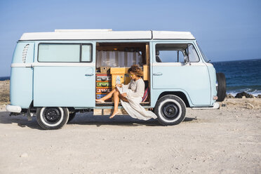 Spain, Tenerife, woman sitting in van parked at seaside - SIPF01718