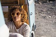 Spain, Tenerife, portrait of woman wearing sunglasses sitting in van - SIPF01721
