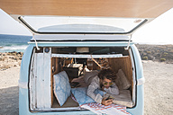 Spain, Tenerife, woman with cell phone lying in van parked at seaside - SIPF01733