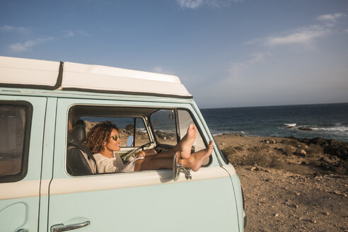 Spain, Tenerife, woman sitting with feet up in van parked at seaside - SIPF01736