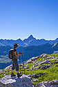 Germany, Bavaria, hiker at Koblat at Nebelhorn with Hochvogel Mountain in background - WGF01109