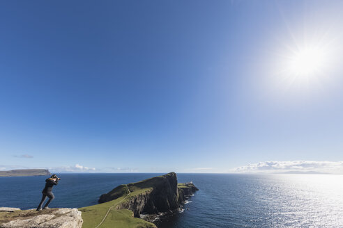 UK, Scotland, Inner Hebrides, Isle of Skye, tourist taking picture of lighthouse at Neist Point - FOF09333