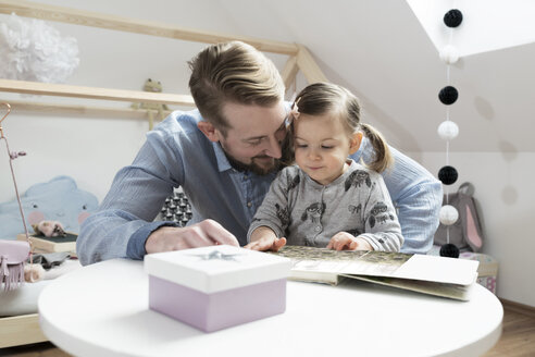 Father and daughter looking at photo album in her nursery - SBOF00591